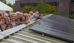 Enkele bewoners bij de zonnepanelen tijdens de opening.