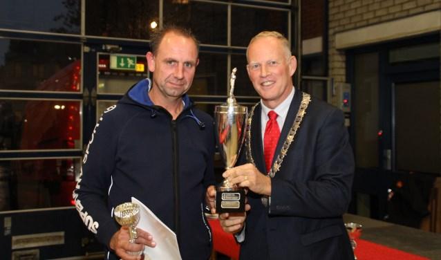 Weesp krijgt de Tempo-trofee uit handen van de burgemeester van Gooise Meren.