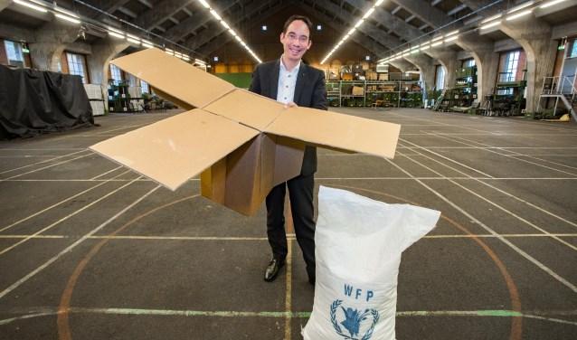 Barry Koperberg laat in de hangar van de Korporaal van Oudheusden Kazerne - waar vrijdag het concert ook is - de dozen zien die drones in gebieden kunnen droppen waar een transportvliegtuig niet meer kan komen.