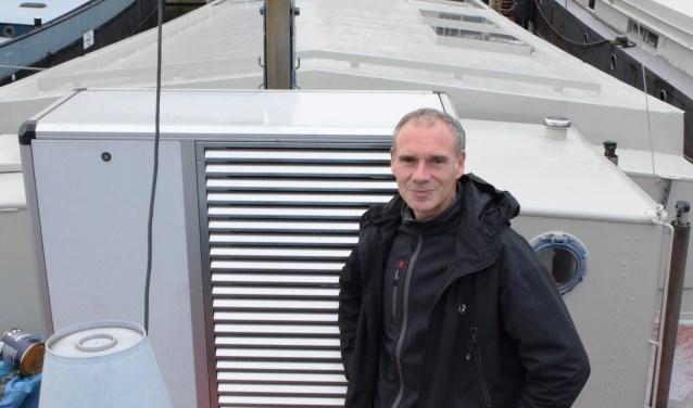 Evert Jan de Vries op de plecht van zijn woonschip, naast de warmtepomp.