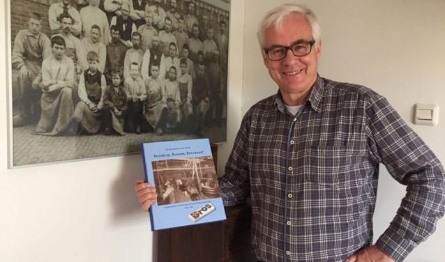 Hans Jonker met het boek bij een foto van werknemers van Bensdorp in vroegere tijden.