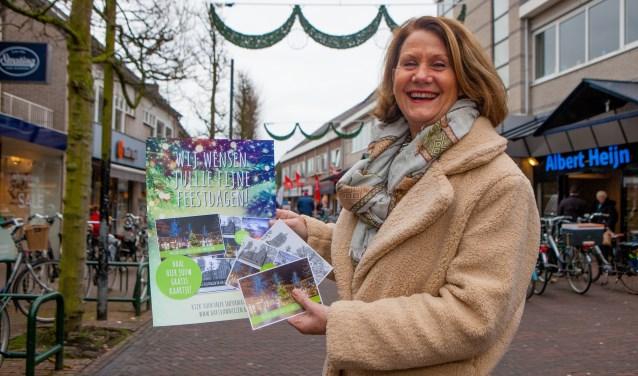 Agnes Haverkort toont de drie kerstkaarten van de actie 'Lieve kerstwensen door Huizers voor Huizers'.