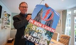Timo Smit, voorzitter van Larens Behoud, met de actieposters om een fusie tegen te gaan.