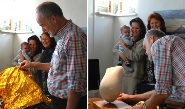 Terwijl Hans Burggraaff het beeld uitpakt, kijken Max, zijn moeder Sonja en beeldhouwster Anna van Roomen toe.