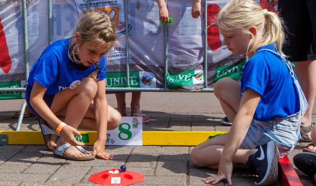 Twee jongedames in de strijd voor het knikkerkampioenschap van Huizen.
