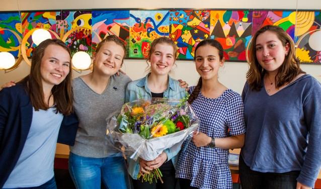 Avigal met enkele klasgenoten en de bos bloemen die ze van de wethouder heeft kregen.
