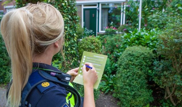 De wijkagent vult een waarschuwingsfolder in, waar ze aankruist waar bewoners op moeten letten.