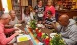 Op dinsdag verzorgen Simone en Rosi (achter staand) altijd een warme lunch-maaltijd in de fleurige en gezellige huiskamer.