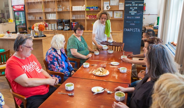 Mark serveert zijn zelfgemaakte soep. Linksachter aan tafel in het groen gastvrouw Anneke.