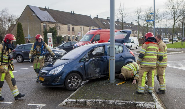 De brandweerlieden bekijken de auto met de gescheurde benzinetank.