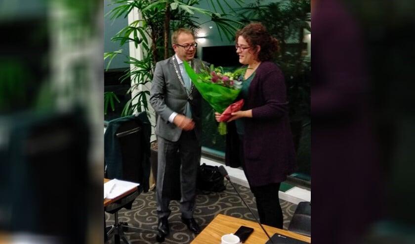 Bloemen van burgemeester Van Benthem voor vertrekkend raadslid Beppie Hoek.