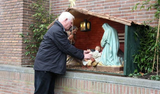 Kees Kuijpers rangschikt de buitenkerststal van de Weesper parochie.