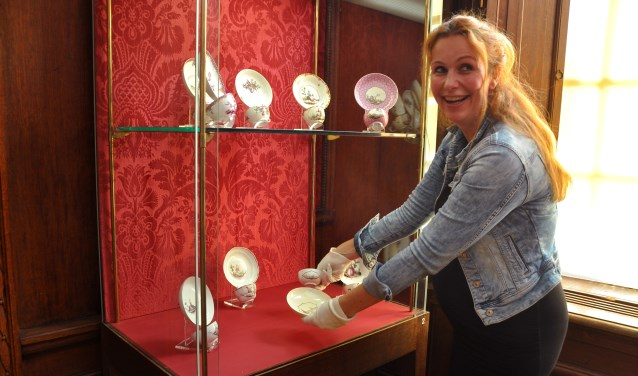 Conservator Lisette Zijp plaatst het nieuwe pronkstuk in de vitrine.