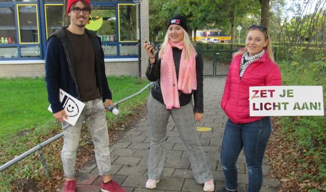 Mees, Else-Meike en Willemijn spoten met spuitkrijt de tekst 'Zet je licht aan' op fietspaden rond scholen.