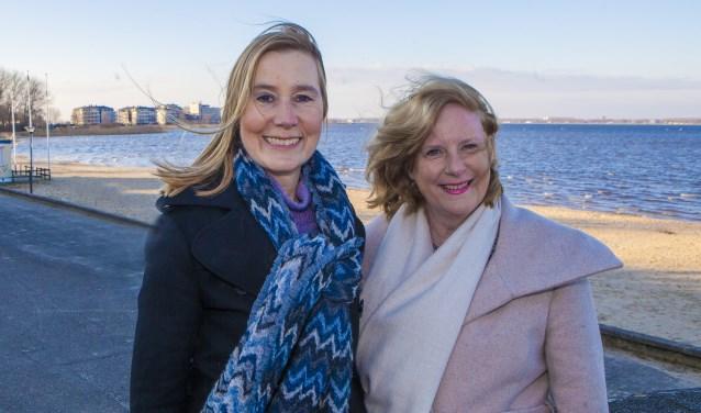 Lijsttrekkers Jessica Prins van de VVD (links) en Marlous Verbeek van D66 trotseren de straffe wind voor een foto bij het strand.