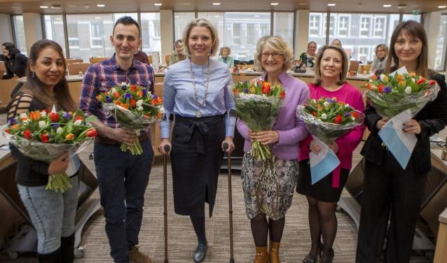 De nieuwe Nederlanders op de foto met de wethouder.
