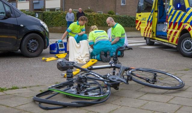 Ambulancepersoneel behandelt de aangereden wielrenner.