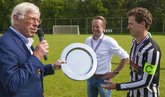 Wethouder Ton Stam overhandigt de kampioenschaal.
