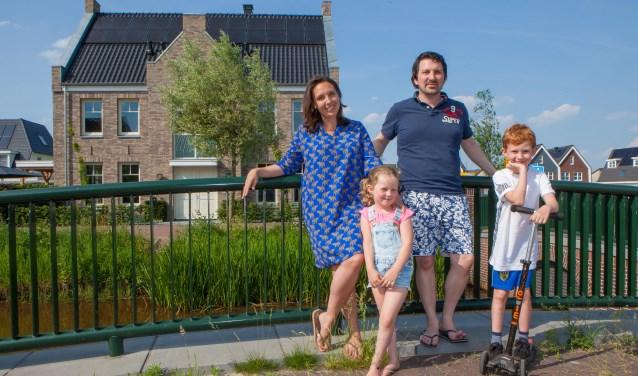 Saskia en Justin en hun kinderen in de Zuidpolder. Op de achtergrond hun nieuwe woning.