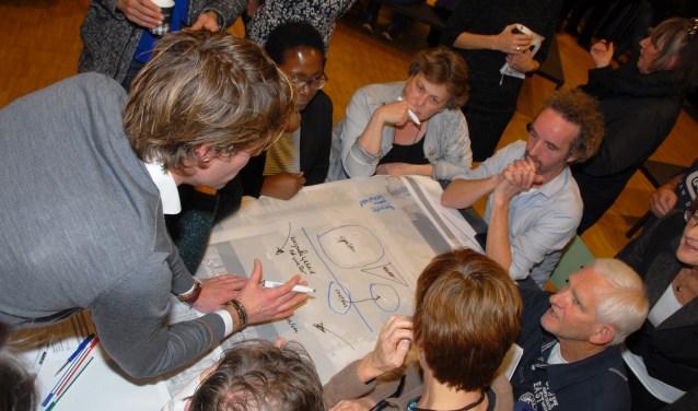 Olivier Lauteslager (op de rug gezien) overlegt met buurtbewoners tijdens een van de informatieavonden.