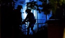 De politie in actie tijdens de inval bij de woning aan de Larenseweg.