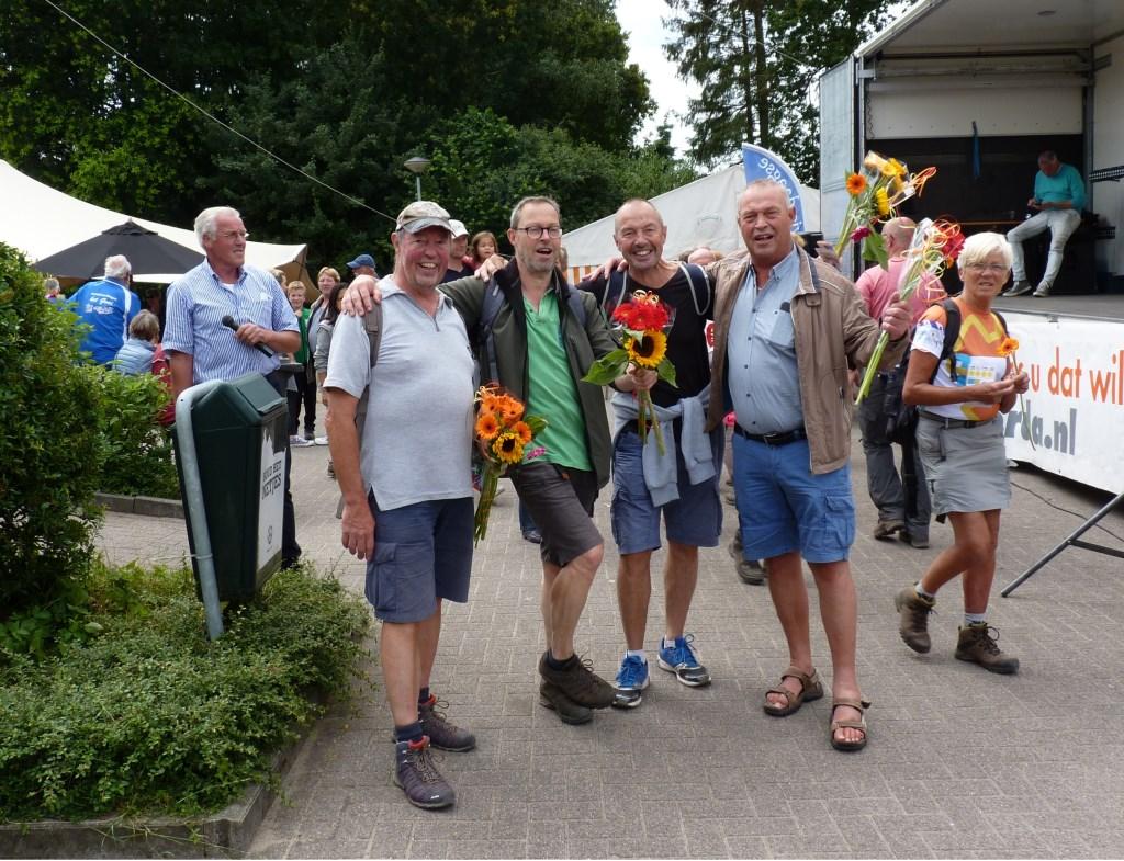 Cock (r) verwelkomt zijn broers Jan, Arnold en Gerard Smit met fleurige boeketten.