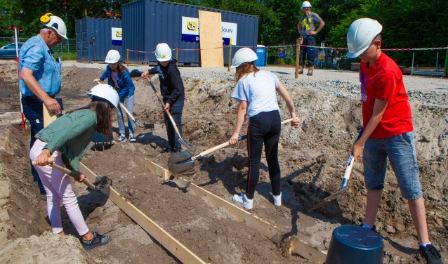 Leerlingen helpen bij het leggen van het fundament van de school.