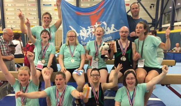 De groep succesvolle turners met hun medailles.