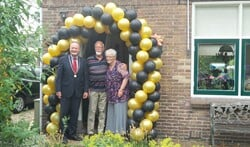 Het echtpaar Klijn-Kuit met de burgemeester voor de versierde voordeur.