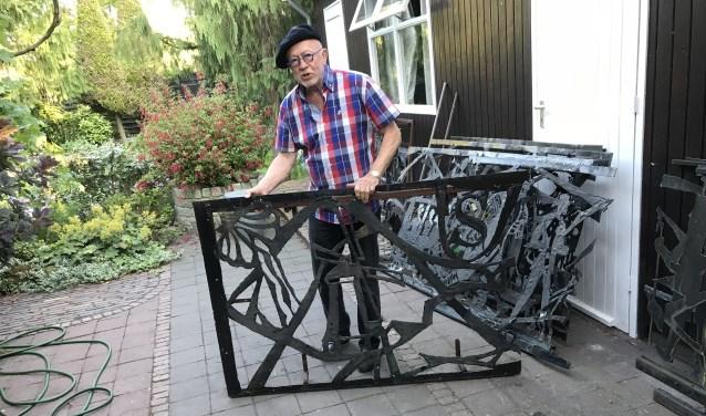Tekenleraar Hans van Deuren met een deel van het kunstwerk dat hij redde van de sloop. De molen en het wapen van Laren zijn duidelijk herkenbaar.