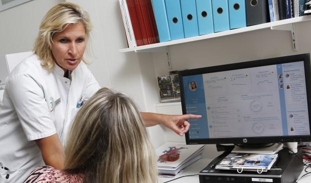 Interventiecardioloog Karin Arkenbout geeft tekst en uitleg aan een patiënt.