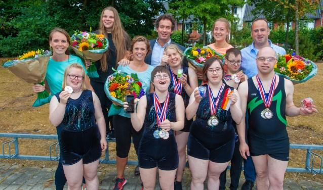 De trotse turners met medailles en de wethouder.