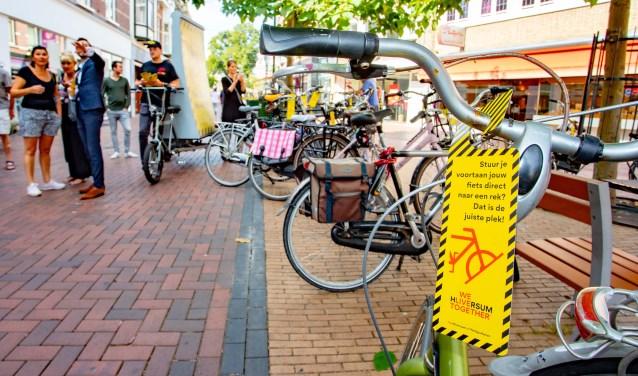 Geel-zwarte hangers op verkeerd geparkeerde fietsen. Nu is het nog waarschuwen geblazen.