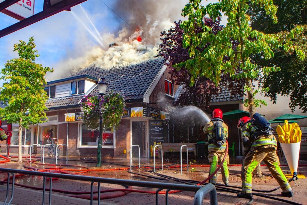 De brandweer is met man en macht in de weer om de brand te blussen.