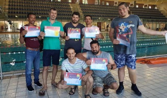 De vluchtelingen tonen hun zwemdiploma.