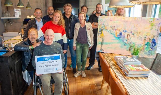 Het merendeel van de ondernemers en de kunstenaar met zijn schilderij dat werd geveild.