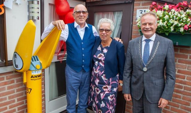 Jan en Renée met de burgemeester voor de deur van hun huis, waar de Wegenwachtpaal herinnert aan het werk van Jan bij de ANWB.