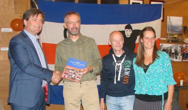 Wethouder Floris Voorink (links) neemt het eerste exemplaar van het jubileumboek in ontvangst uit handen van Marinus Kamphorst vergezeld door medecommissieleden Wim Dral en Anneleen Post.