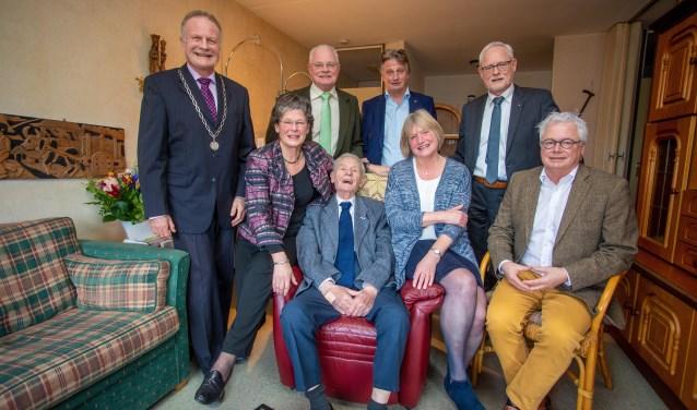 Harrie Schepens is het feestelijk middelpunt tussen zijn kinderen en met de burgemeester op de foto.