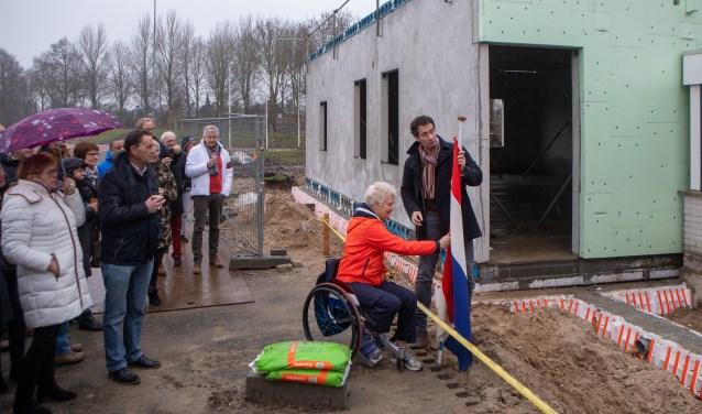 Wethouder Roland Boom en atleet Djoke van Marum staan klaar om de vlag te hijsen om het hoogste punt van de nieuwbouw te vieren.