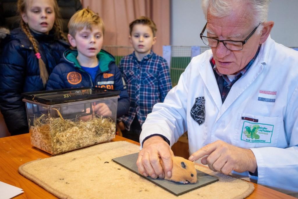 Het werk van de keurmeester wordt aanschouwt door de kinderen.