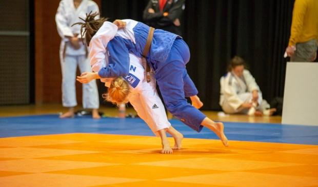 Nadiah in het wit zet een worp in tijdens het NK Judo -21.