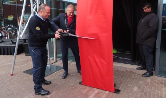 Burgemeester Sicko Heldoorn en supermarktmanager Jack knippen het lint door.