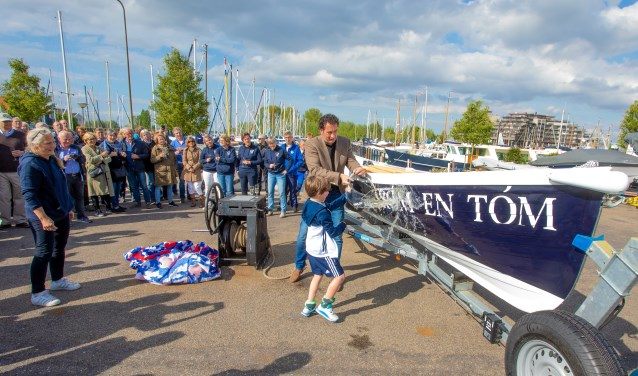 Wethouder Roland Boom doopt de boot met wat hulp. Links voorzitter Erica de Vries.