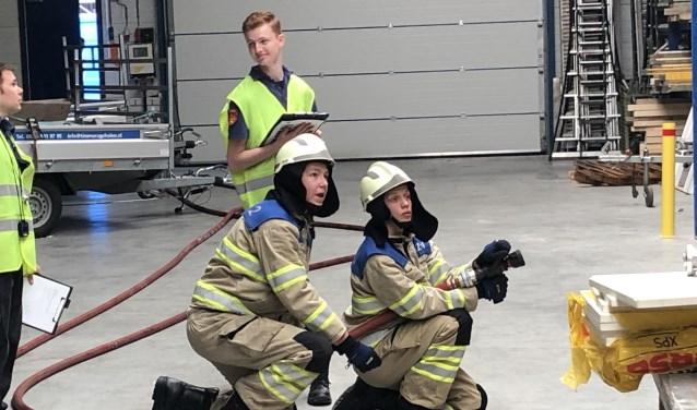 Floris Jan Weijermans (rechts) en Thijs Brasser van jeugdbrandweer Huizen in actie.