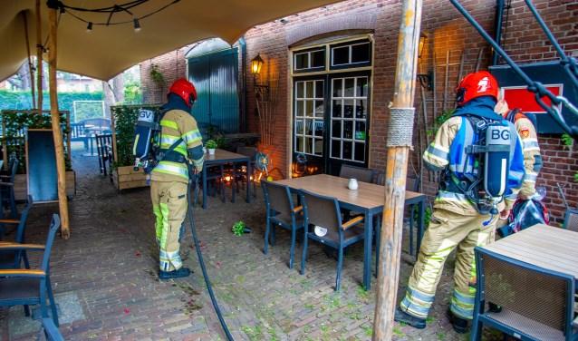 De brandweer blust de plantenbak.