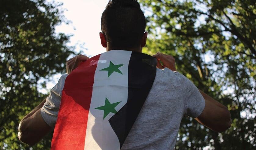 Een man met de vlag van Syrië.