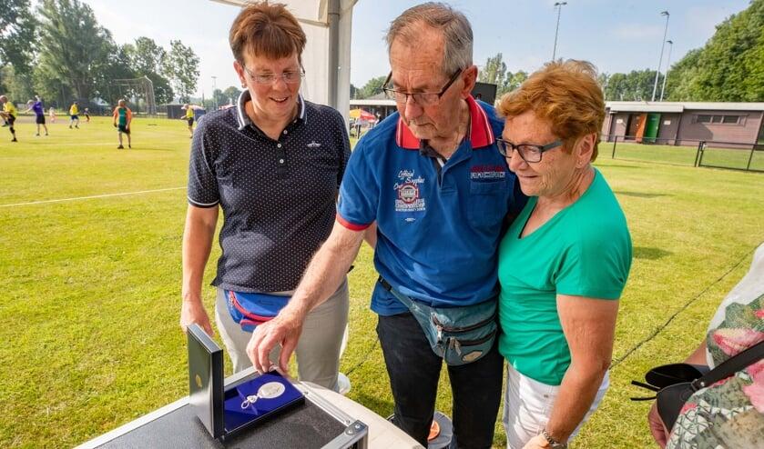 Oud-voorzitter Appie Knol en zijn vrouw bekijken de Erepenning. Knol was tevens eregast tijdens het toernooi.