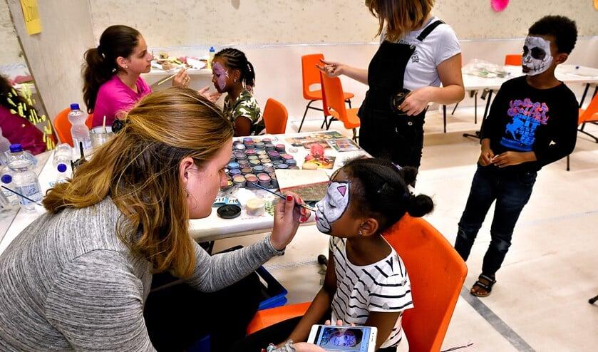 Een begeleidster schminkt een meisje.