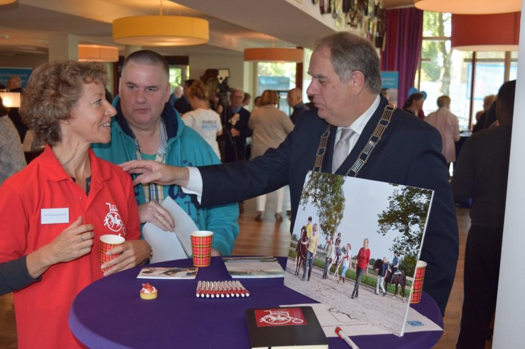 Wnd. burgemeester Bas Verkerk onderhoudt zich met Stichting Ariane de Ranitz, de organisatie die paardrijlessen aanbiedt voor mensen met een beperking.  © De Vierklank